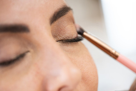 Close up of a make up artist applying eye shadow to her client
