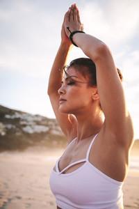 Woman meditating at the beach