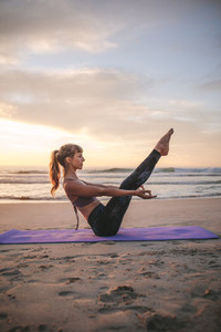 Woman doing boat yoga pose on the beach
