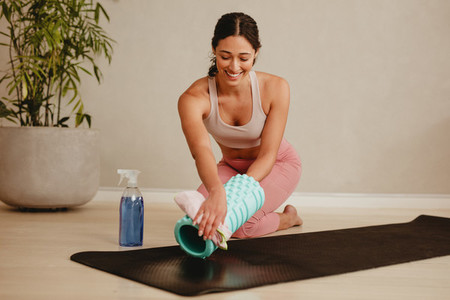 Gym member cleaning and sanitizing exercising equipment