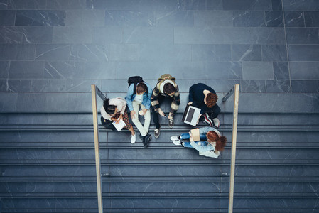 Students studying on stairs at college