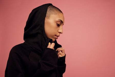 Androgynous woman in black hoodie