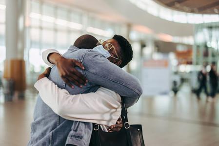 Tourist couple giving goodbye hug at airport