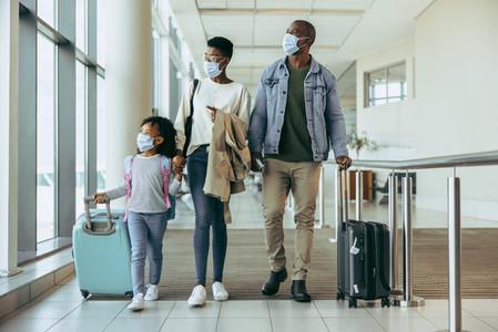 Tourist family walking through passageway in airport
