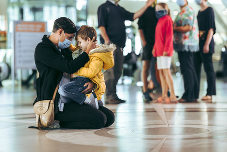 Woman with her son at airport during pandemic