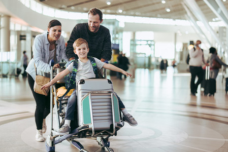 Parents pushing luggage trolley with their son at airport
