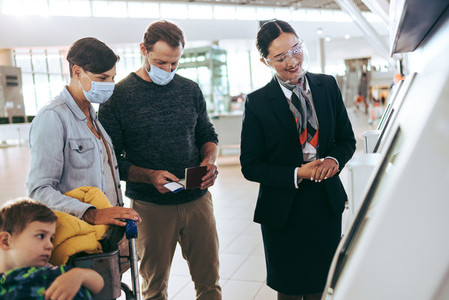 Airport staff helping family at self check in machine