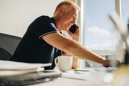Senior businessman having a phone call at his desk