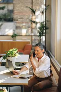 Entrepreneur talking on cell phone in office