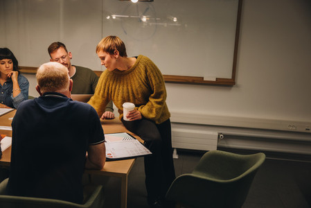 Businesswoman sharing ideas with team in meeting