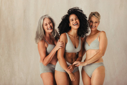 Smiling women of different ages embracing their natural bodies