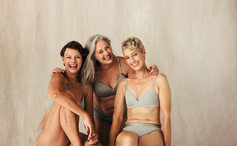 Three happy and confident women embracing their aging bodies