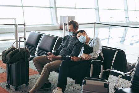 Traveler couple in pandemic waiting at airport terminal