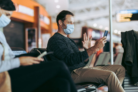 Traveler in face mask at airport doing video call