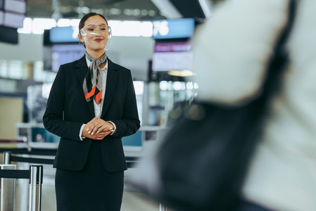 Flight attendant with glass shield at airport