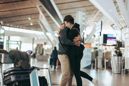 Woman hugging man after arrival from trip