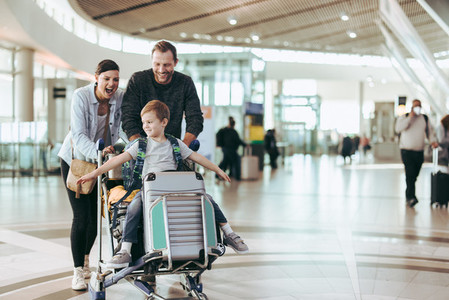Couple pushing trolley with their child at airport