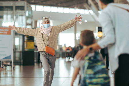 Senior woman welcoming her family at airport after pandemic