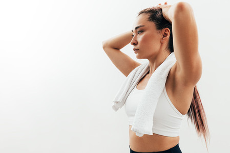Portrait of an Asian woman relaxing during a workout  Tired sportswoman with white towel on neck