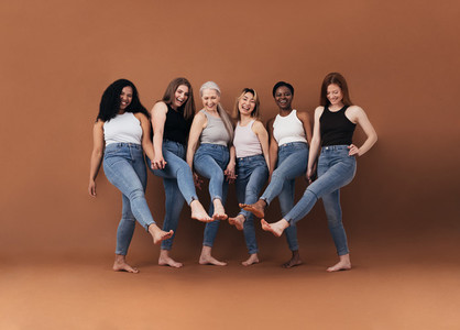 Six multi ethnic women having fun together against brown background