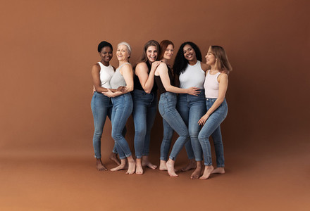 Group of multi ethnic women in casuals posing together against a brown background