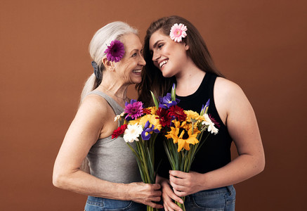 Two women of different ages with bouquets and flowers in their hair looking at each other