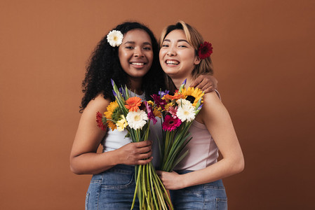 Two young women of different races with bouquets and flowers in their hair posing against a brown background
