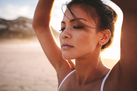 Fit woman sitting on beach and meditating