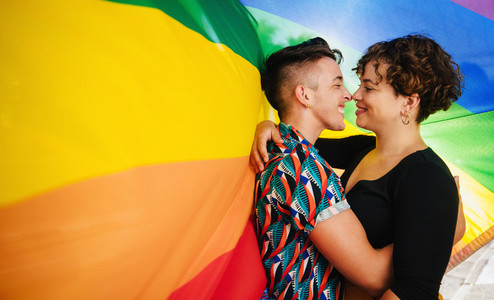 Affectionate queer lovers bonding against a rainbow flag