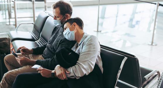 Passenger couple wearing face masks waiting for delayed flight