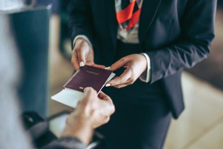 Ground staff checking passport of tourist at airport