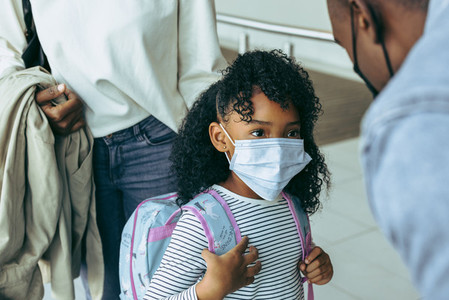 Girl at airport wearing face mask  with family