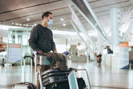 Man with luggage trolley waiting at airport