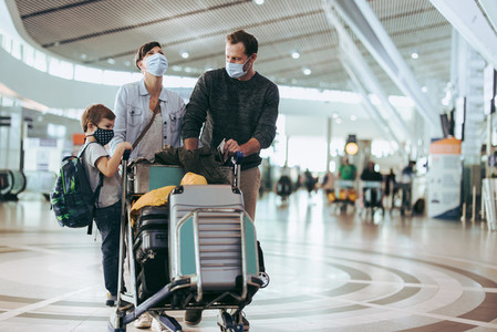 Family walking at airport with luggage trolley