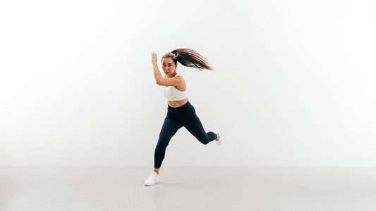 Asian woman jumping from side to side indoors