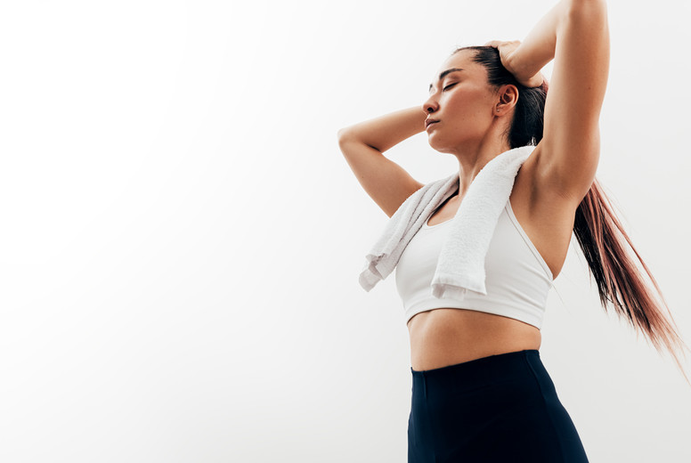 Exhausted woman with closed eyes and towel on neck relaxing after exercises