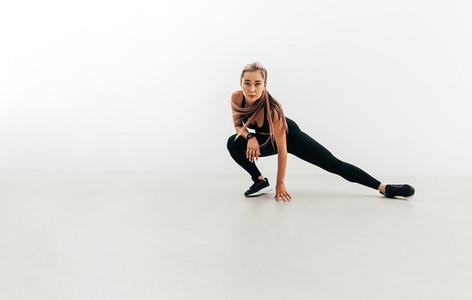 Sportswoman doing stretching exercises indoors before training