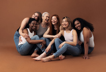 Portrait of six laughing women of different ages and body types sitting together on a brown background in studio