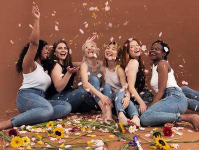 Multi ethnic group of happy women sitting under falling petals