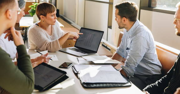 Female executive showing data to team in meeting