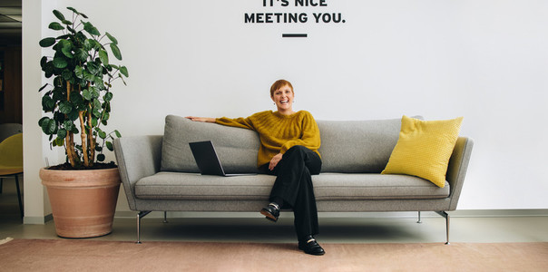 Smiling businesswoman sitting on sofa in office lobby