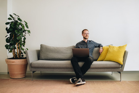 Businessman with laptop sitting on sofa in office