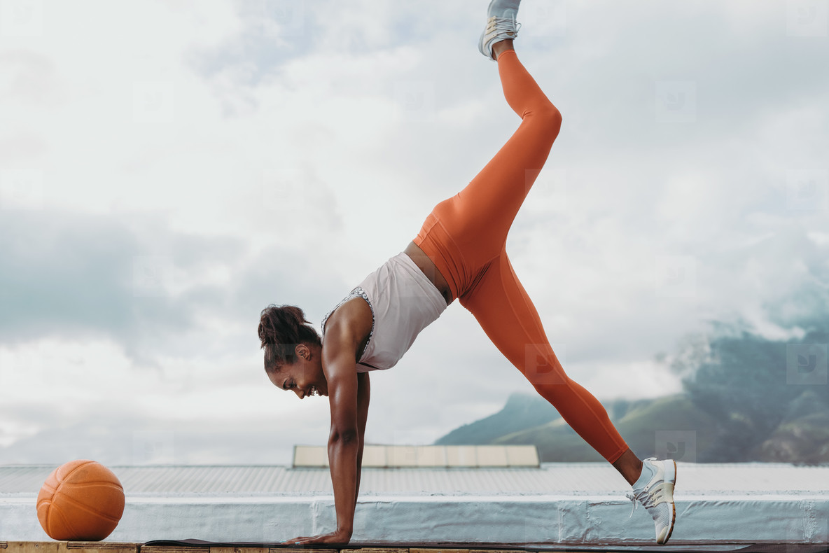 Fit woman doing yoga workout on terrace