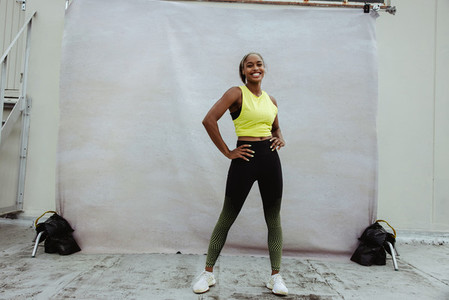 Confident fitness woman on building terrace