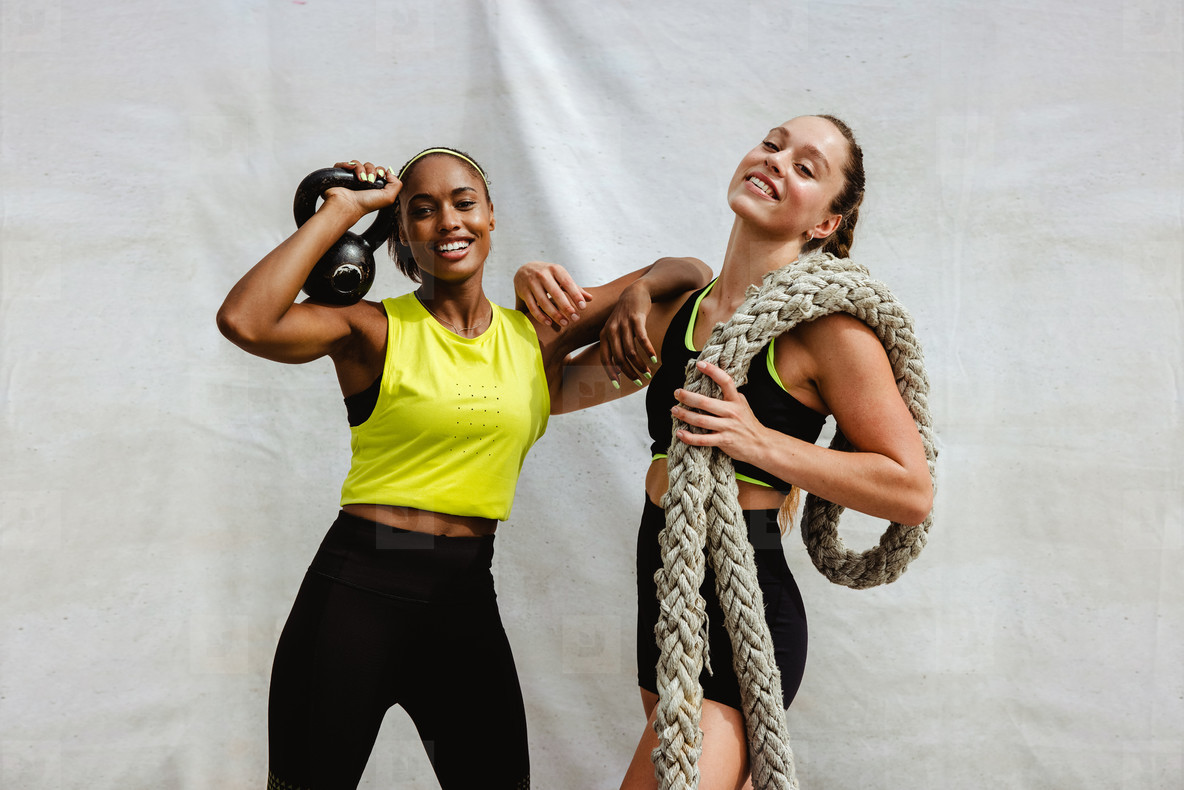 Two sports women with kettlebell and battle rope