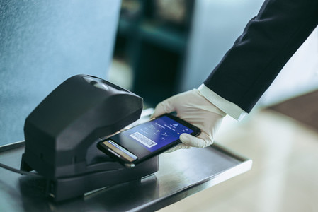 Hand of airport staff scanning boarding pass