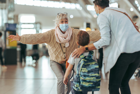 Senior woman welcoming her daughter and grandchild at airport