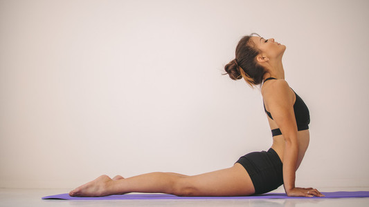 Fit woman practices yoga asana indoors