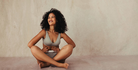 Cheerful young woman embracing her natural body
