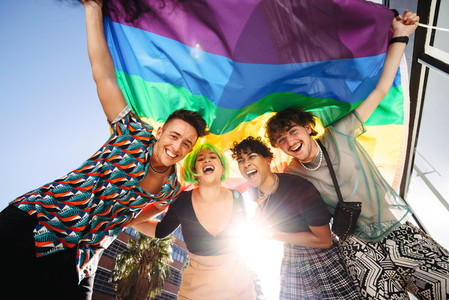 Cheerful LGBTQ people celebrating with the rainbow flag
